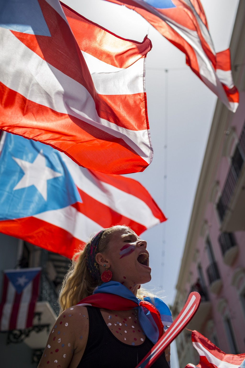 A demonstrator, Puerto Rican national flags waving above her, protests in front of the governor's mansion La Fortaleza, in San Juan, Puerto Rico, Wedn...