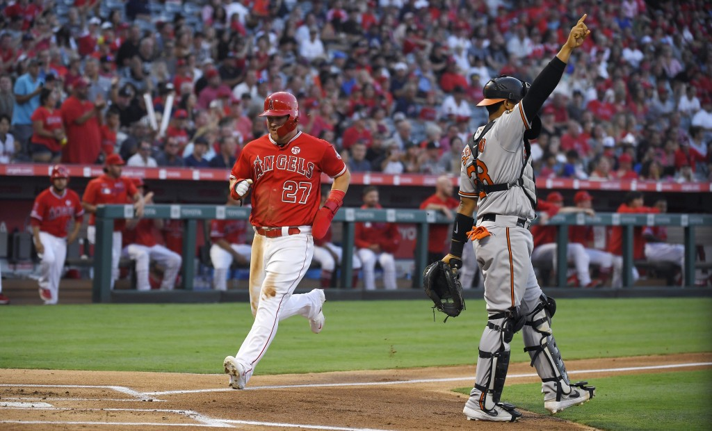 Los Angeles Angels' Mike Trout, left, scores on a sacrifice fly by Justin Upton as Baltimore Orioles catcher Pedro Severino gestures during the first ...