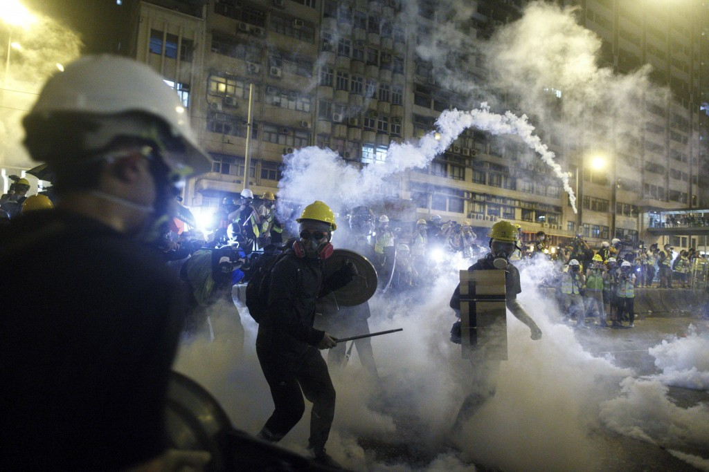 In this July 21, 2019, photo, protesters react to tear gas during a confrontation with riot police in Hong Kong. Hong Kong police launched tear gas at...