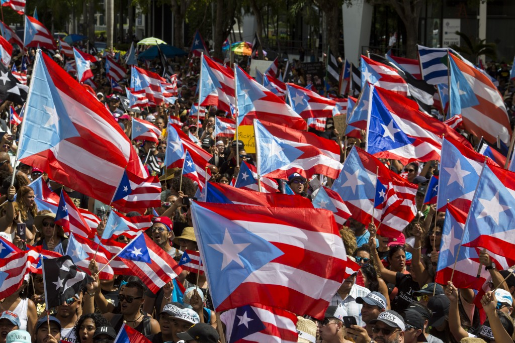 People march with Puerto Rican national flags to celebrate the resignation of Gov. Ricardo Rossello who announced overnight that he is resigning Aug. ...