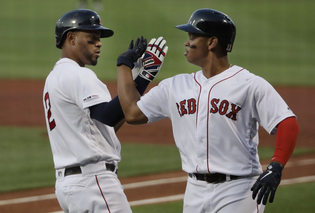 Boston Red Sox's Xander Bogaerts, left, celebrates his three-run homer with teammate Rafael Devers in the first inning of a baseball game against the ...