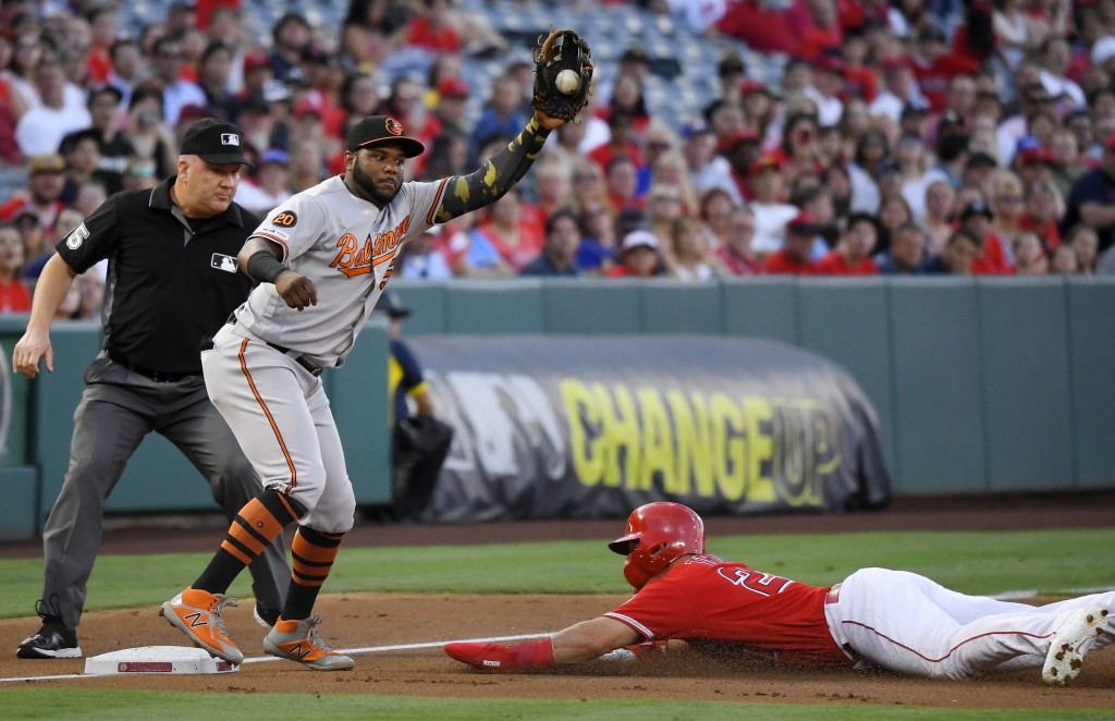Los Angeles Angels' Mike Trout, right, dives safely into third on a wild pitch as Baltimore Orioles third baseman Hanser Alberto takes a late throw du...