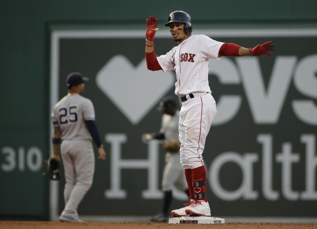 Boston Red Sox's Mookie Betts celebrates after hitting a two-run double as New York Yankees second baseman Gleyber Torres (25) looks to the outfield i...