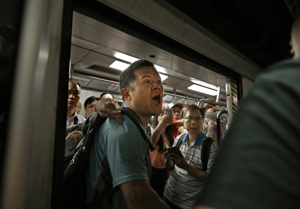 In this July 24, 2019, photo, a passenger reacts after protesters blocked the train doors stopping the trains leaving at a subway platform in Hong Kon...
