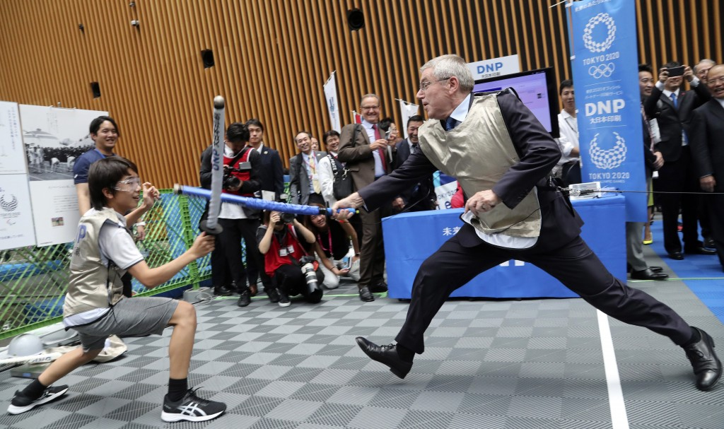 In this July 24, 2019, photo, IOC President Thomas Bach, right, demonstrates fencing with Japanese junior high school student Yui Hashimoto during a O...