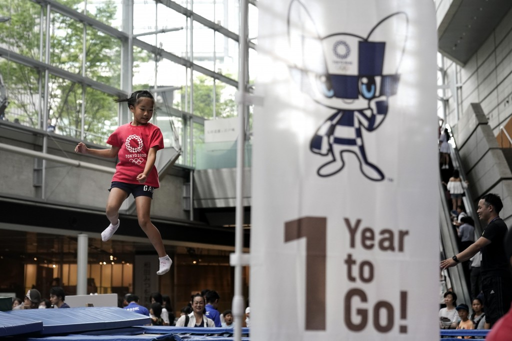 In this July 24, 2019, photo, a girl plays on a trampoline during a One Year to Go ceremony held at Tokyo International Forum to mark one year until t...