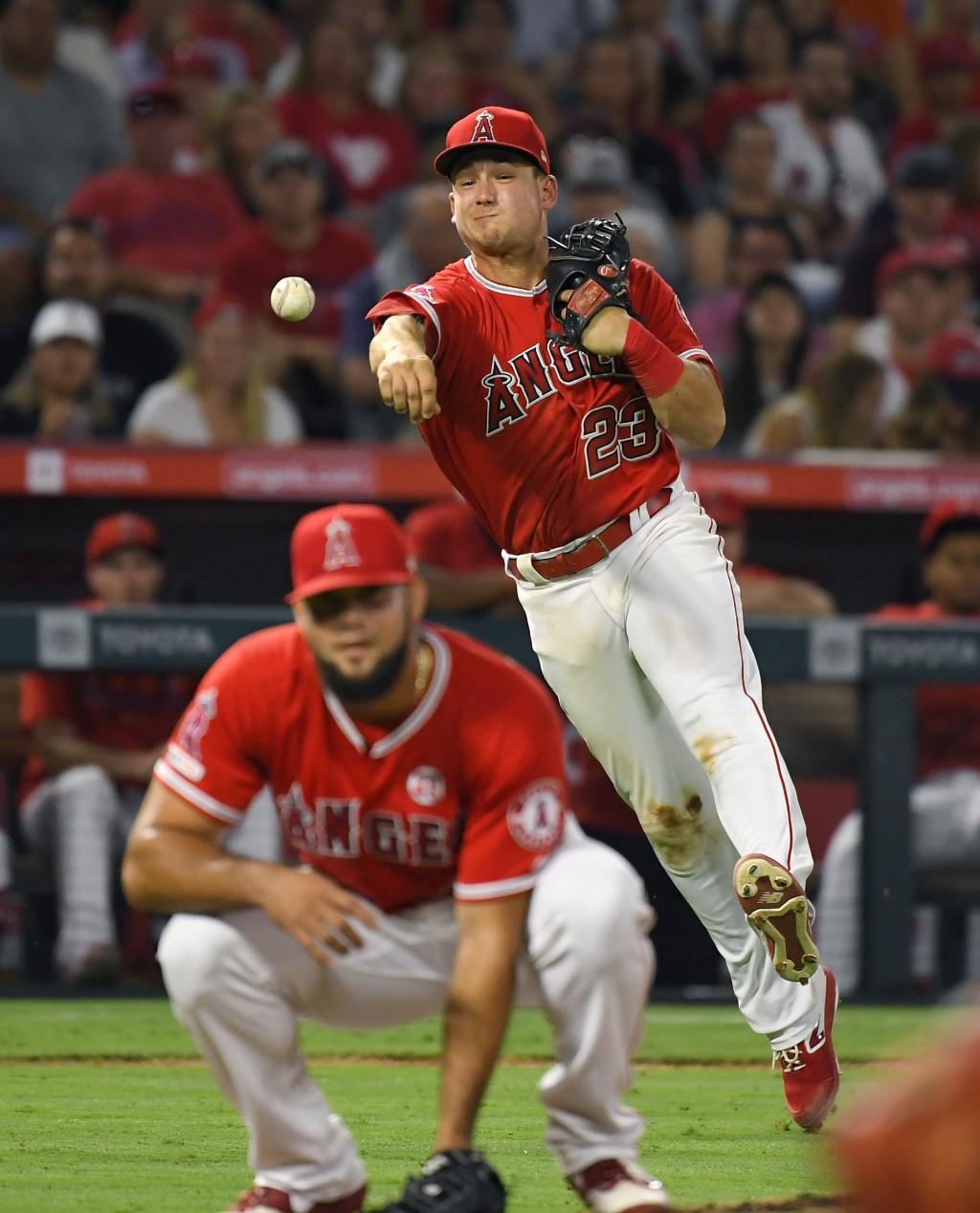 Los Angeles Angels third baseman Matt Thaiss, top, throws out Baltimore Orioles' Trey Mancini as Los Angeles Angels relief pitcher Luis Garcia ducks d...