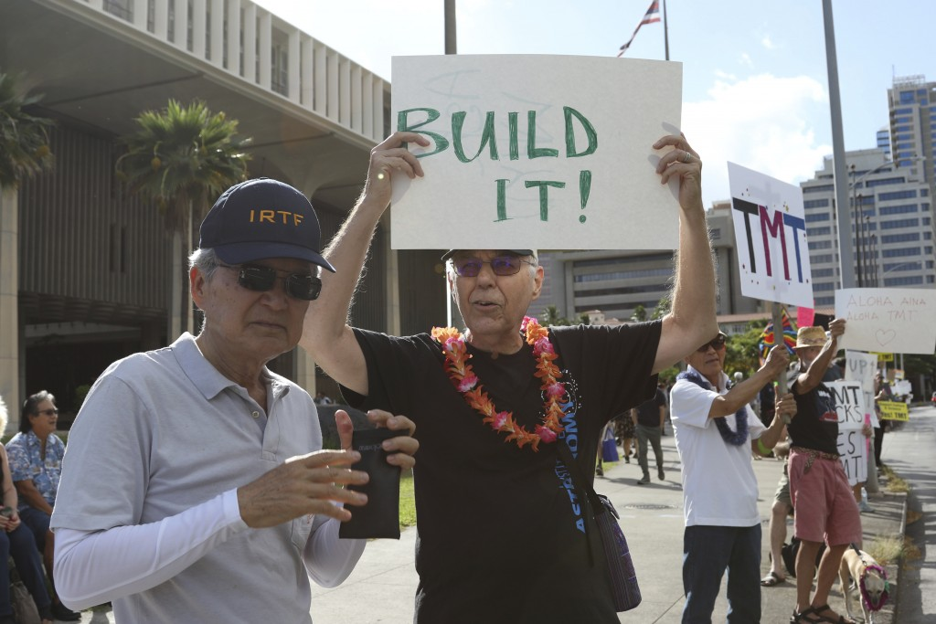 "Astronomers Alan Stockton, center, holding a sign saying ""Built It!,"" and Alan Tokunaga, left, join a rally in support the Thirty Meter Telescope outs..."