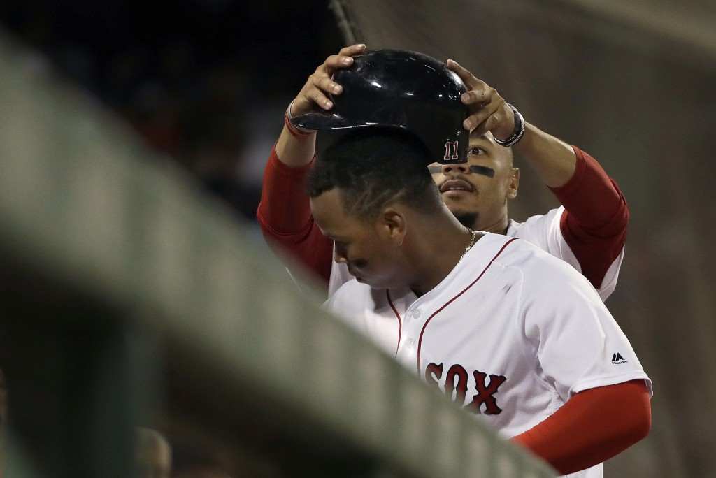 Boston Red Sox's Rafael Devers has his helmet taken off by teammate Mookie Betts in celebration of Devers' solo home run in the fourth inning of a bas...