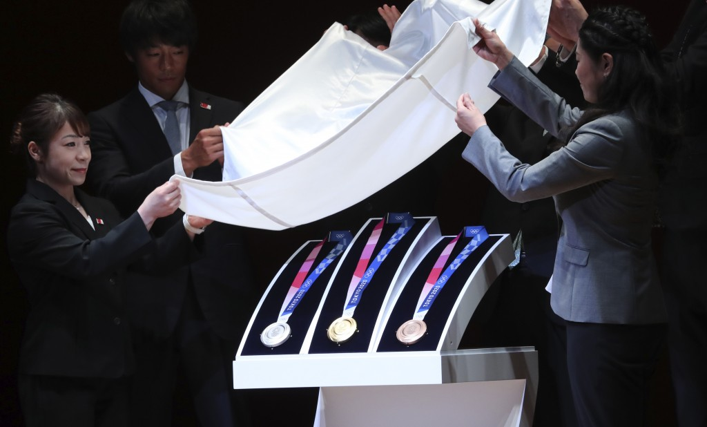 In this July 24, 2019, photo, Tokyo 2020 Olympic medals are unveiled during the One Year to Go Olympic ceremony in Tokyo. Gold, silver, and bronze Oly...