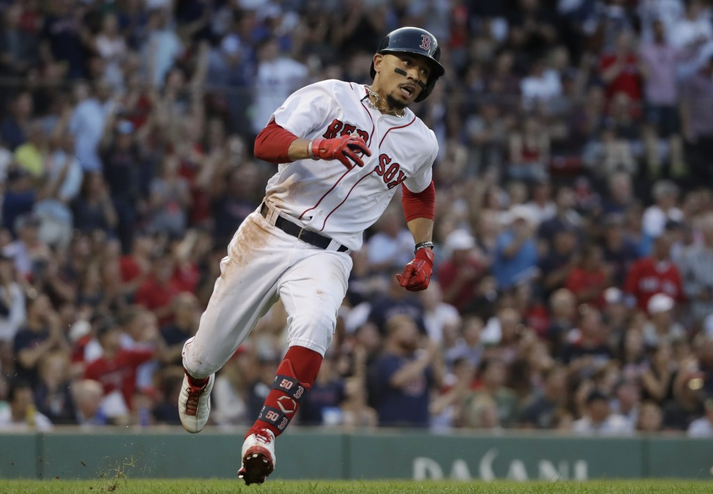 Boston Red Sox's Mookie Betts runs after hitting a two-run double in the first inning of a baseball game against the New York Yankees at Fenway Park, ...