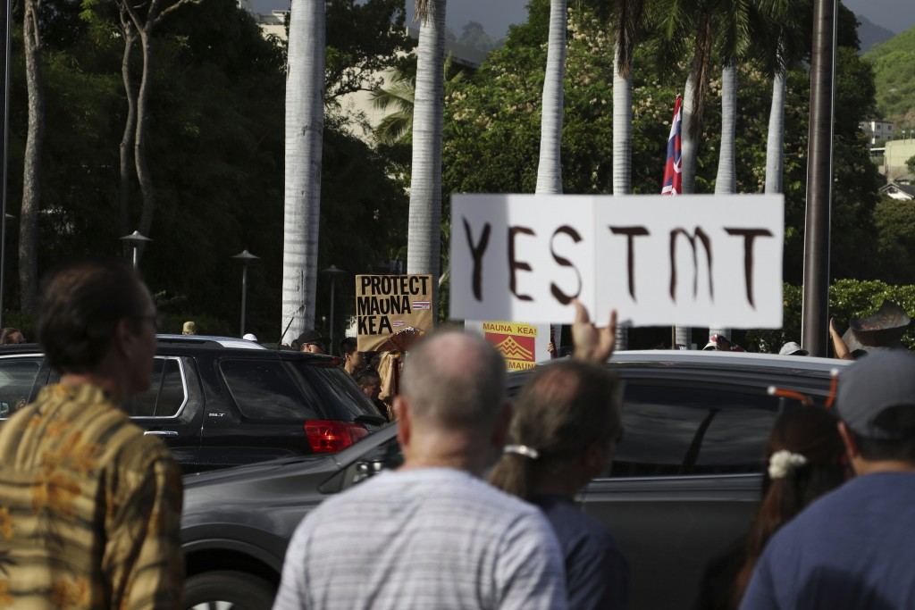 Supporters of the Thirty Meter Telescope, foreground, gather for a rally outside the Hawaii State Capitol in Honolulu on Thursday, July 25, 2019, as o