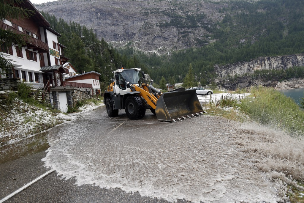 A worker uses a snow shovel to clean the road of the nineteenth stage of the Tour de France cycling race over 126,5 kilometers (78,60 miles) with star...