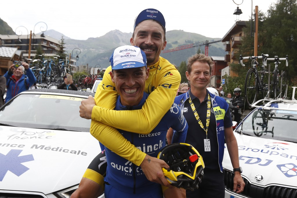 France's Julian Alaphilippe, wearing the yellow jersey jokes with Spain's Enric Mas during the nineteenth stage of the Tour de France cycling race in ...