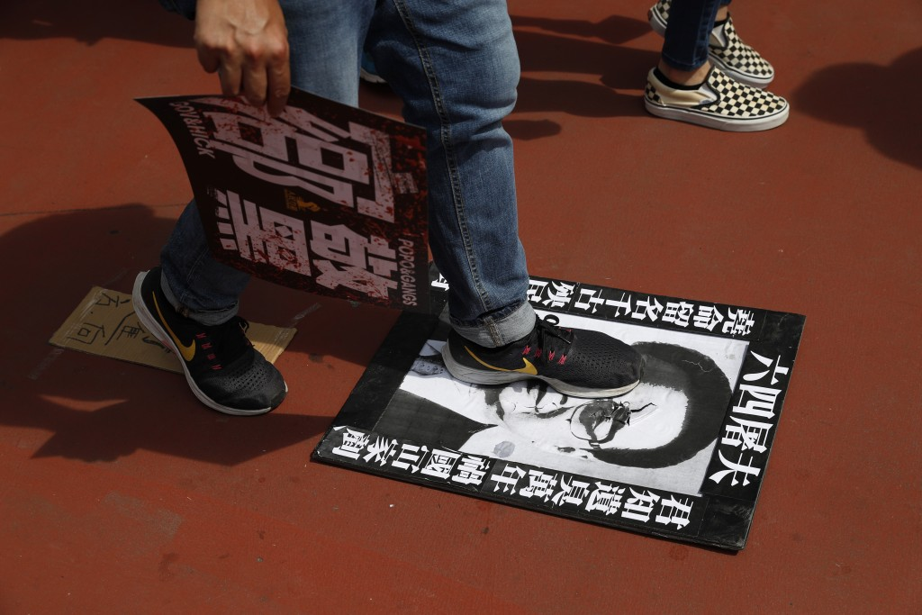"""A protester steps on a poster depicting former Chinese Premier Li Peng with the words """"June 4th Butcher"""" who recently passed away, during a rally In H..."""