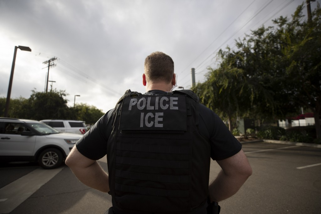FILE - In this July 8, 2019, file photo, a U.S. Immigration and Customs Enforcement (ICE) officer looks on during an operation in Escondido, Calif.  A...