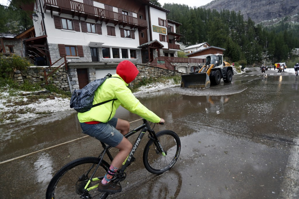 A supporter rides on a bicycle as a worker uses a digger to clean the road of the nineteenth stage of the Tour de France cycling race over 126,5 kilom...
