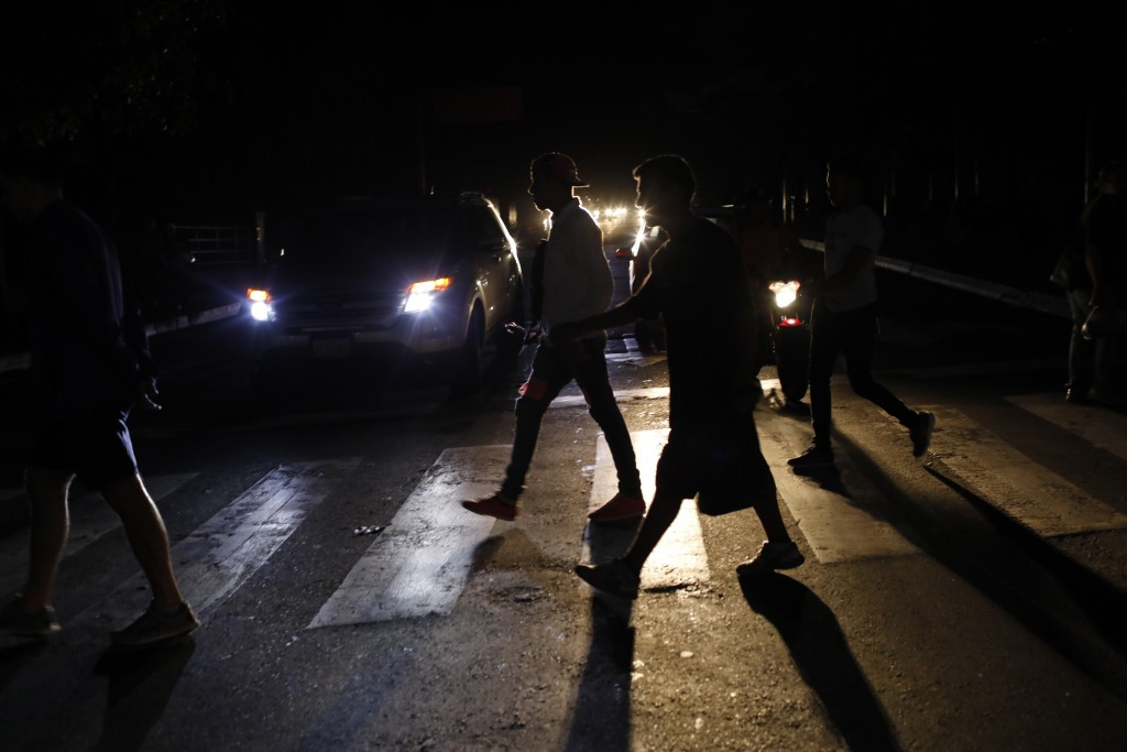 FILE - In this Monday, July 22, 2019, file photo, people walk on a street during a blackout in Caracas, Venezuela. When much of Venezuela was plunged ...