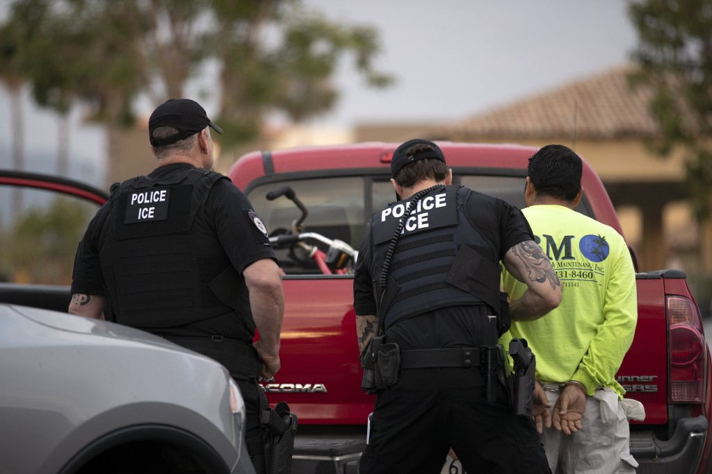 In this July 8, 2019, photo, a U.S. Immigration and Customs Enforcement (ICE) officers detain a man during an operation in Escondido, Calif.  A sweepi...