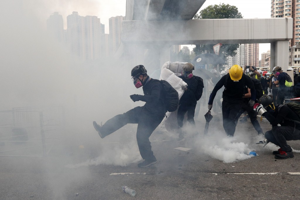 Protesters kick back and pick up tear gas canisters during a face off with riot police at Yuen Long district in Hong Kong Saturday, July 27, 2019. Pol...
