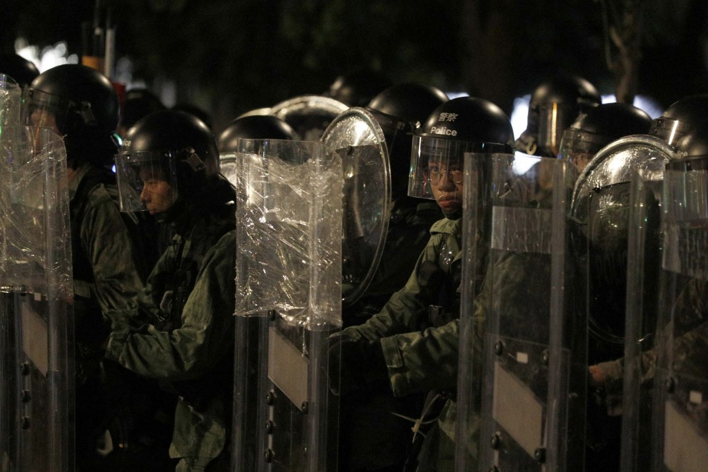 Riot police stand behind shields as they face off protesters in Yuen Long district in Hong Kong on Saturday, July 27, 2019. Police in Hong Kong used t...