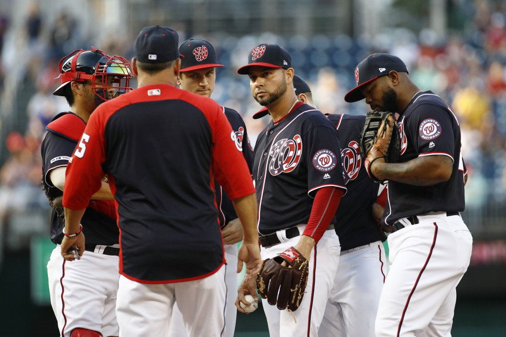 Washington Nationals starting pitcher Anibal Sanchez, center, gathers on the mound with teammates and pitching coach Paul Menhart, second from left, a...