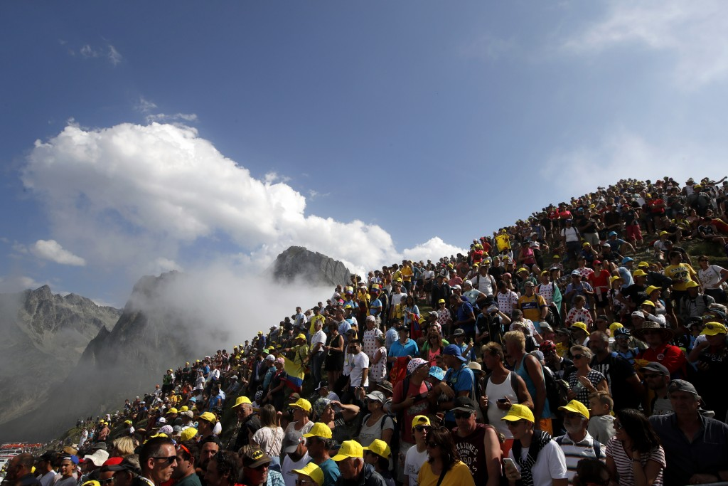 FILE - In this Saturday, July 20, 2019 file photo spectators stand on the Tourmalet pass next to the finish line of the fourteenth stage of the Tour d...