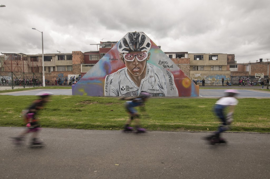 Children skate past a mural of Colombia's Egan Bernal in his hometown in Zipaquira, Colombia, Saturday, July 27, 2019. Barring a crash or a last-minut...