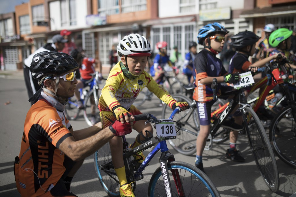 A father helps his son prepare for a race organized in the hometown of Colombia's Egan Bernal to celebrate his performance in the Tour de France cycli...