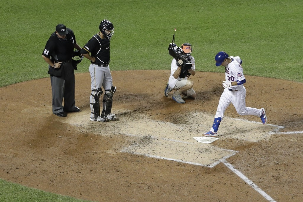 New York Mets' Michael Conforto, right, steps on home plate after hitting a home run during the sixth inning of a baseball game as Pittsburgh Pirates