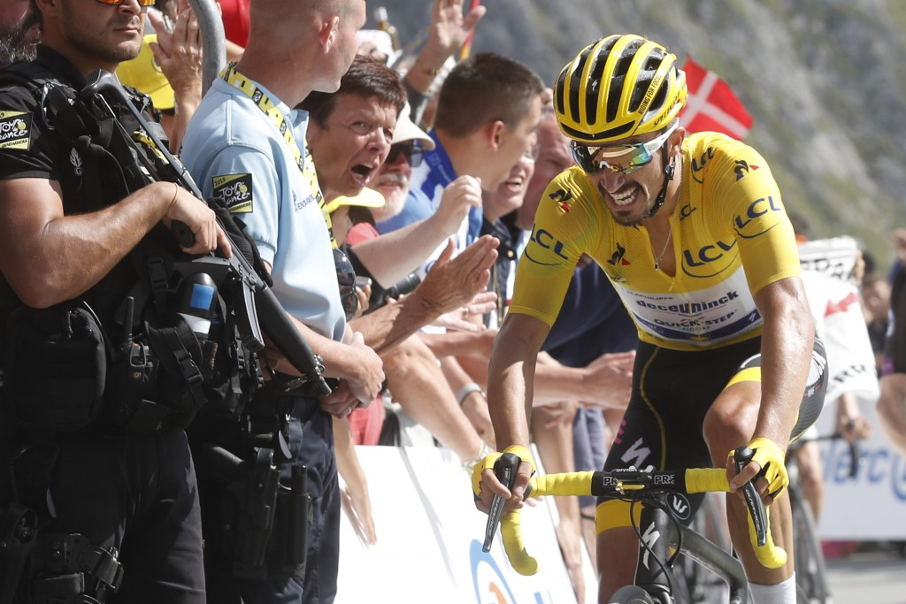 FILE - In this Saturday, July 20, 2019 file photo France's Julian Alaphilippe wearing the overall leader's yellow jersey crosses the finish line of th...