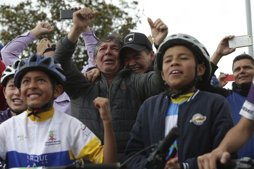 Residents celebrate as they watch on a giant screen Colombia's Egan Bernal performance in the twentieth stage of the Tour de France cycling race at Be...