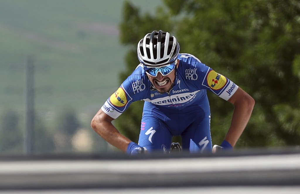 FILE - In this Monday, July 8, 2019 file photo France's Julian Alaphilippe rides to the finish line to win the third stage of the Tour de France cycli...
