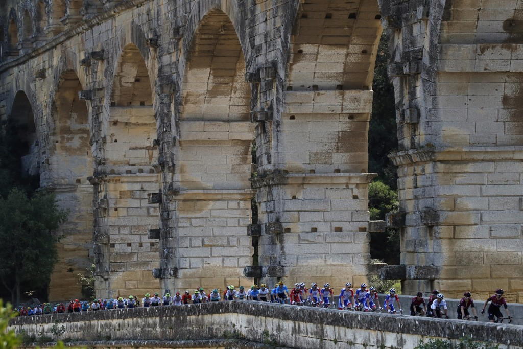 FILE - In this Tuesday, July 23, 2019 file photo the pack rides next to the Pont du Gard during the sixteenth stage of the Tour de France cycling race...