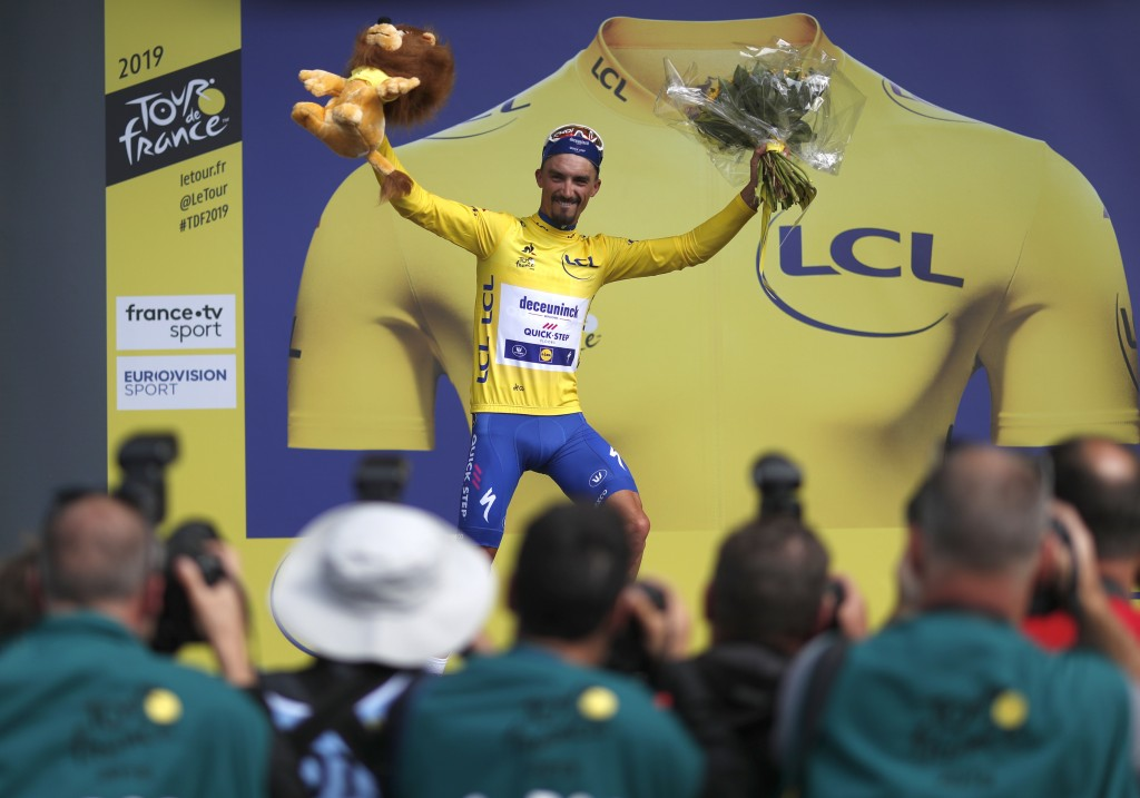 FILE - In this Monday, July 8, 2019 file photo France's Julian Alaphilippe wearing the overall leader's yellow jersey celebrates on the podium after w...