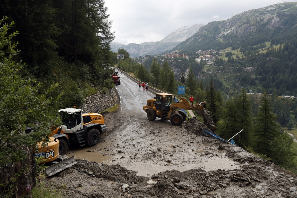 FILE - In this Friday, July 26, 2019 file photo workers use diggers to clean the road of the nineteenth stage of the Tour de France cycling race over ...