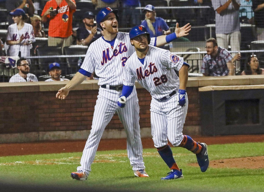 New York Mets' Todd Frazier (21) celebrates with teammate J.D. Davis (28) after they score on a two-run home run by Davis during the seventh inning of...