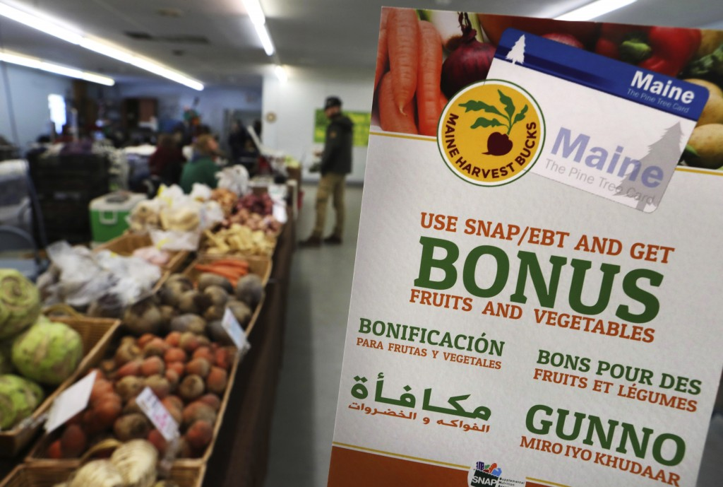 FILE - In this Friday, March 17, 2017, file photo, a sign advertises a program that allows food stamp recipients to use their EBT cards to shop at a f