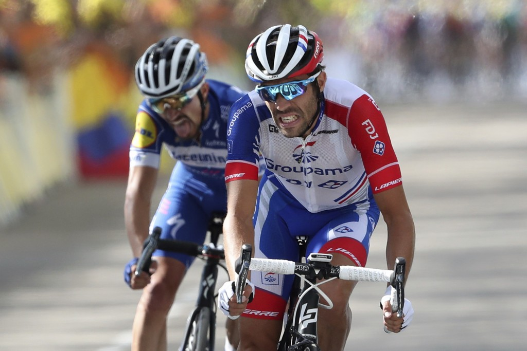 FILE - In this Saturday, July 13, 2019 file photo France's Thibaut Pinot, right, and France's Julian Alaphilippe crosse the finish line of the eighth ...