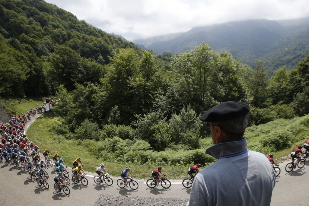 FILE - In this Saturday, July 20, 2019 file photo France's Julian Alaphilippe wearing the overall leader's yellow jersey rides with the pack during th...