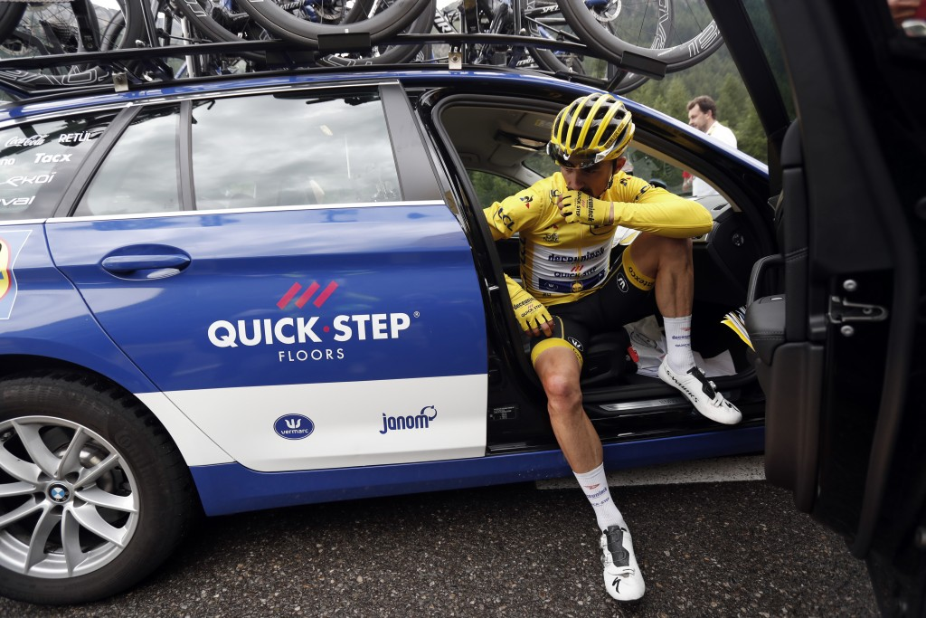 FILE - In this Friday, July 26, 2019 file photo France's Julian Alaphilippe wearing the overall leader's yellow jersey sits in the team director car d...