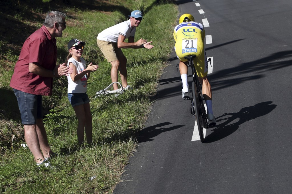 FILE - In this Friday, July 19, 2019 file photo spectators cheers France's Julian Alaphilippe wearing the overall leader's yellow jersey as he rides d...