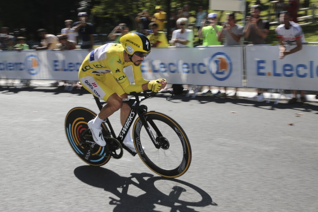 FILE - In this Friday, July 19, 2019 file photo France's Julian Alaphilippe wearing the overall leader's yellow jersey rides during the thirteenth sta...