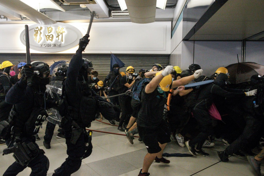 Special Tactical Squad officers attack protesters with batons who refused to disperse from a train station in Yuen Long district in Hong Kong on Satur...
