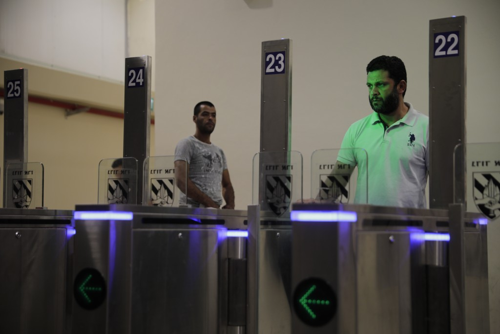 In this Thursday, July 11, 2019 photo, Palestinians stand in front of a biometric gate as they enter Israel at the Qalandia crossing in Jerusalem. Isr
