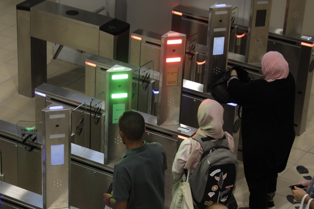 In this Thursday, July 11, 2019 photo, Palestinians cross a biometric gate as they enter into Israel at the Qalandia crossing in Jerusalem. Israel's m...