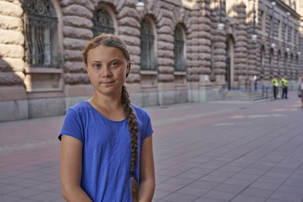 In this photo taken on Friday, July 26, 2019, Greta Thunberg stands next to Swedish parliament in Stockholm. Thunberg, the Swedish teenager whose soci