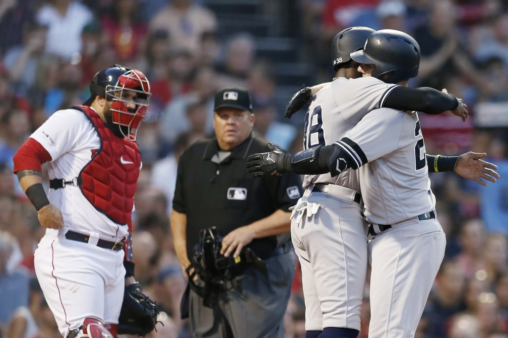 New York Yankees' Austin Romine, right, celebrates his two-run home run that also drove in Cameron Maybin (38) as Boston Red Sox's Sandy Leon, left, l...