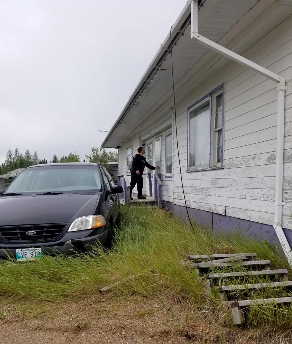 In this recent photo provided by the Royal Canadian Mounted Police, RCMP officers canvas homes and buildings in the Gillam, Manitoba area, as they con...