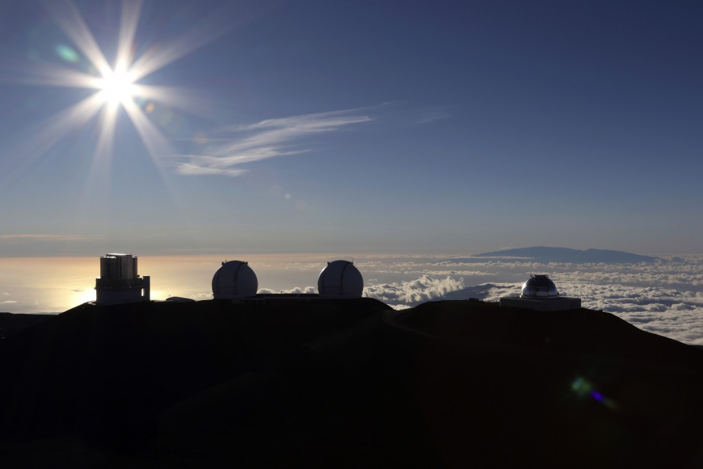 FILE - In this Sunday, July 14, 2019, file photo, the sun sets behind telescopes at the summit of Mauna Kea in Hawaii. The man tasked with trying to f